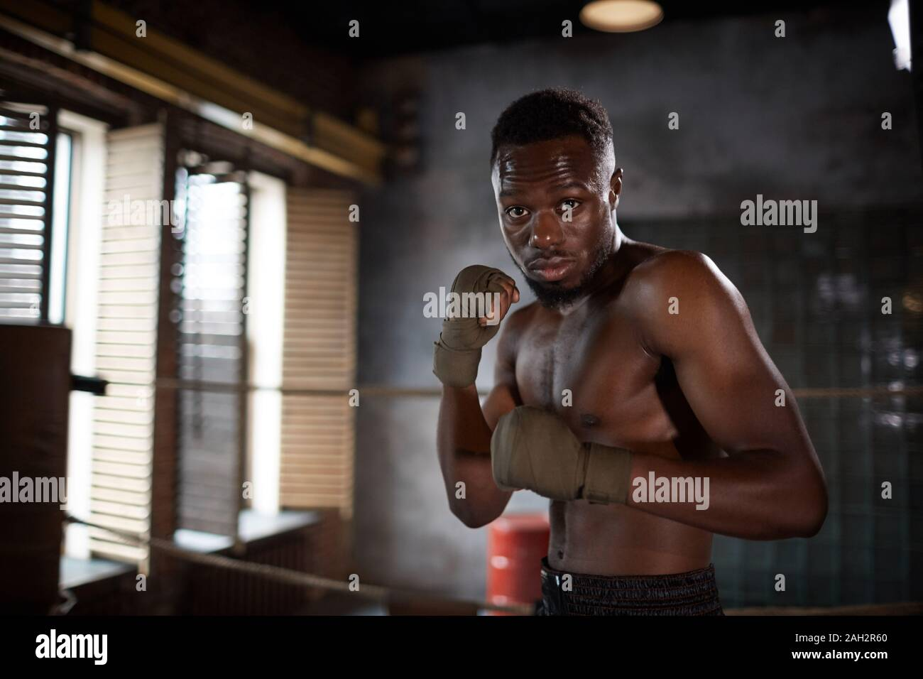 Portrait of African young muscular man standing and posing at camera while training in gym Stock Photo