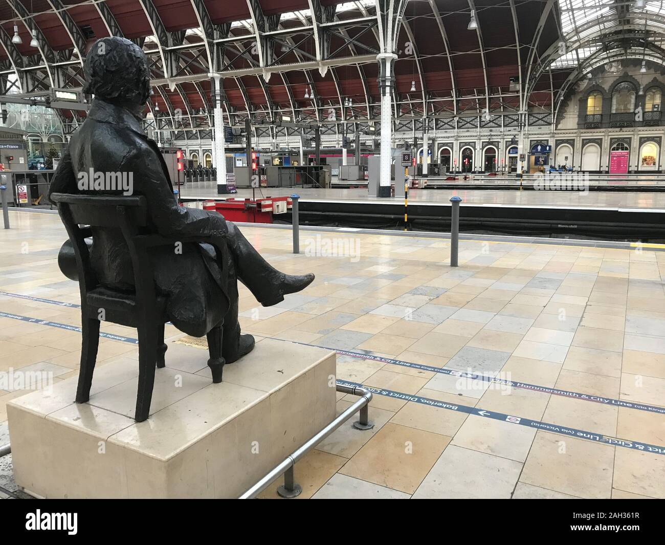 A statue of Isambard Kingdom Brunel looks out over London's Paddington Station which is empty of trains on Christmas Eve because of major engineering work over the holiday period on the railway line between Paddington and Slough. Stock Photo