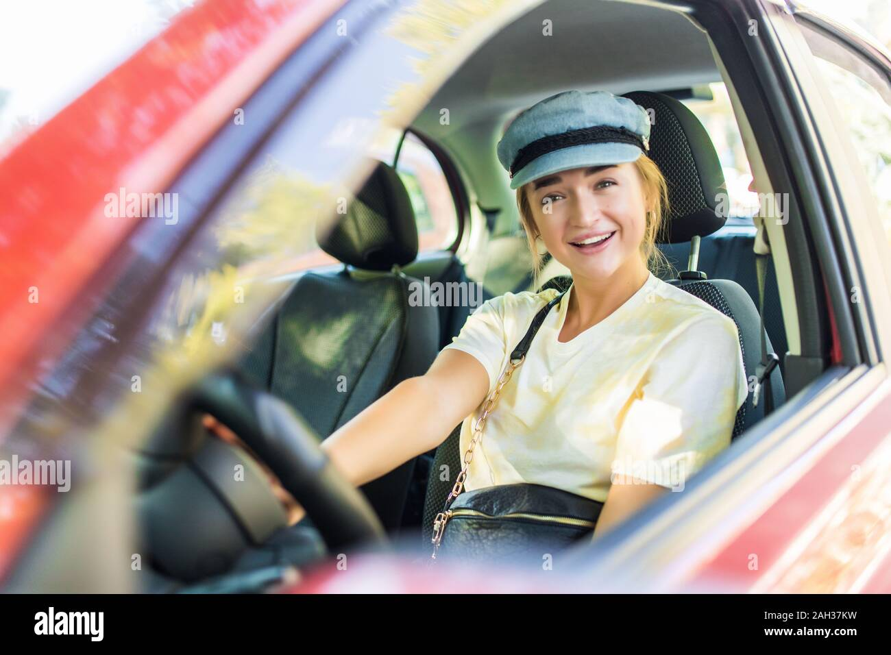 Happy woman driver behind the wheel red car Stock Photo