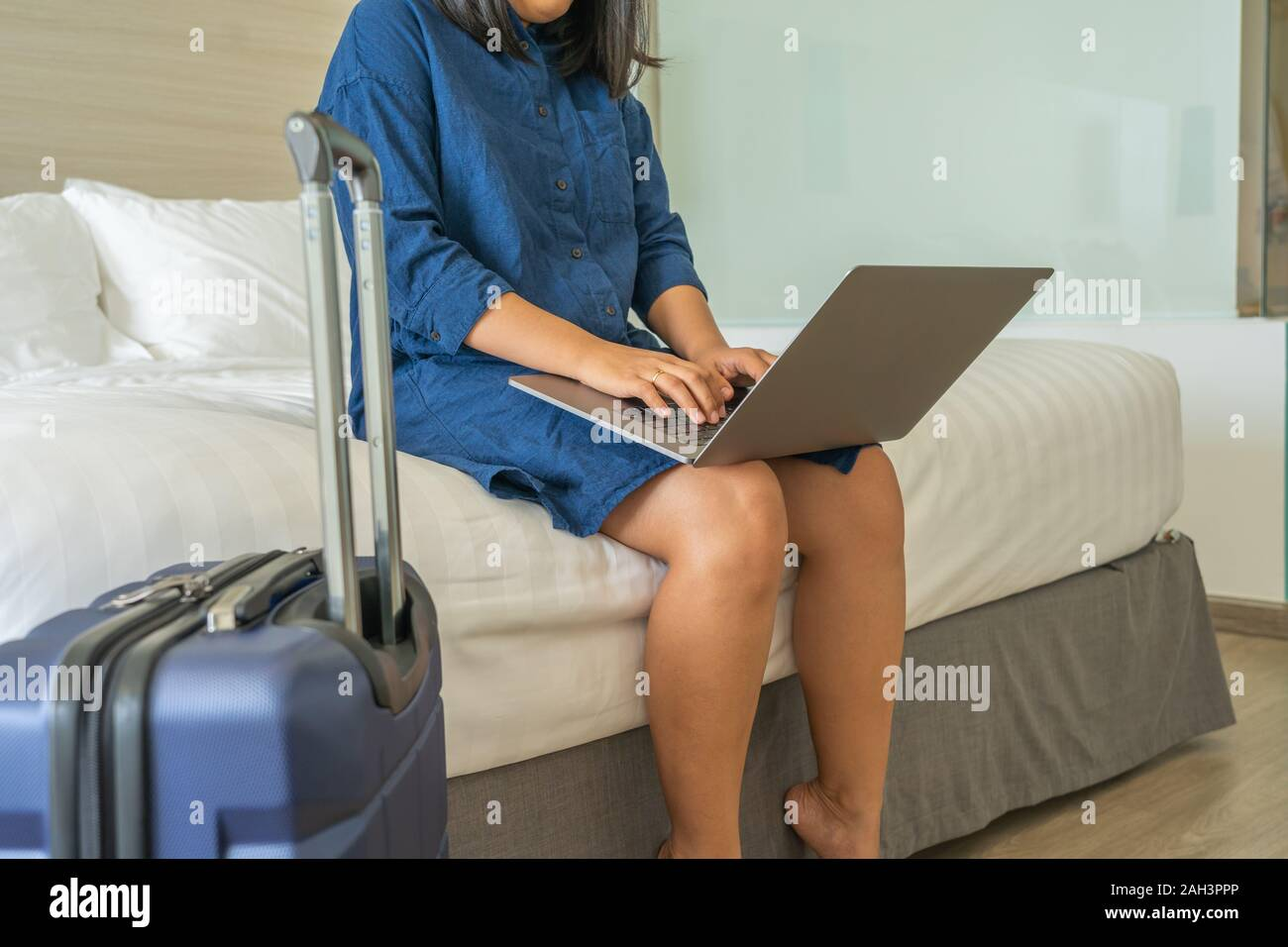 Woman sitting on bed using laptop next to carry-on suitcase Stock Photo