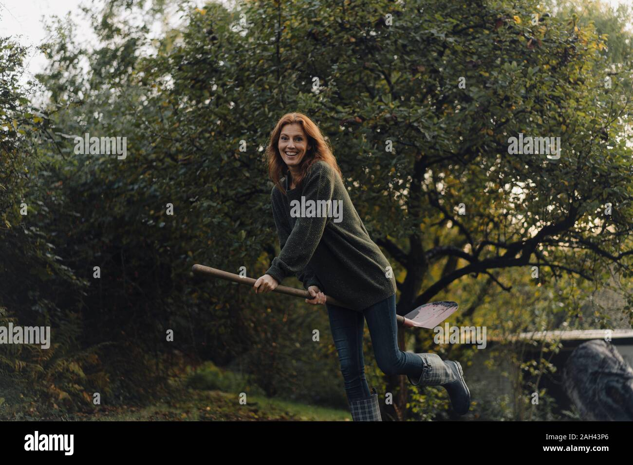 Woman working in her garden, pretending to fly on a shovel Stock Photo