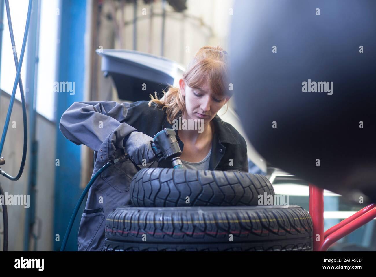 Female car mechanic working in repair garage Stock Photo
