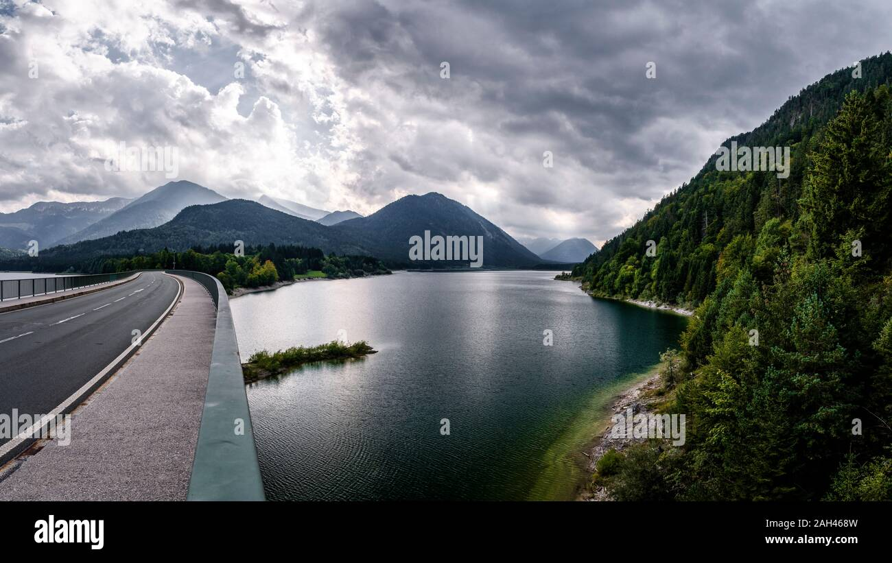 Germany, Bavaria, Cloudy sky over highway crossingSylvenstein Reservoir Stock Photo
