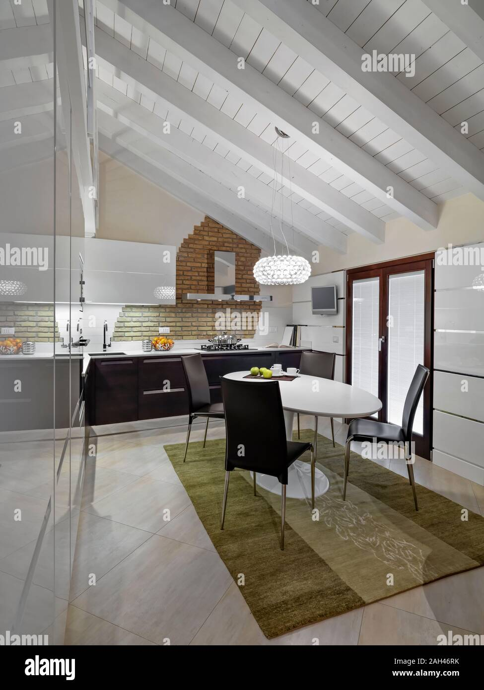 interior shot of a modern kitchen in the attic room with dining table and carpet Stock Photo
