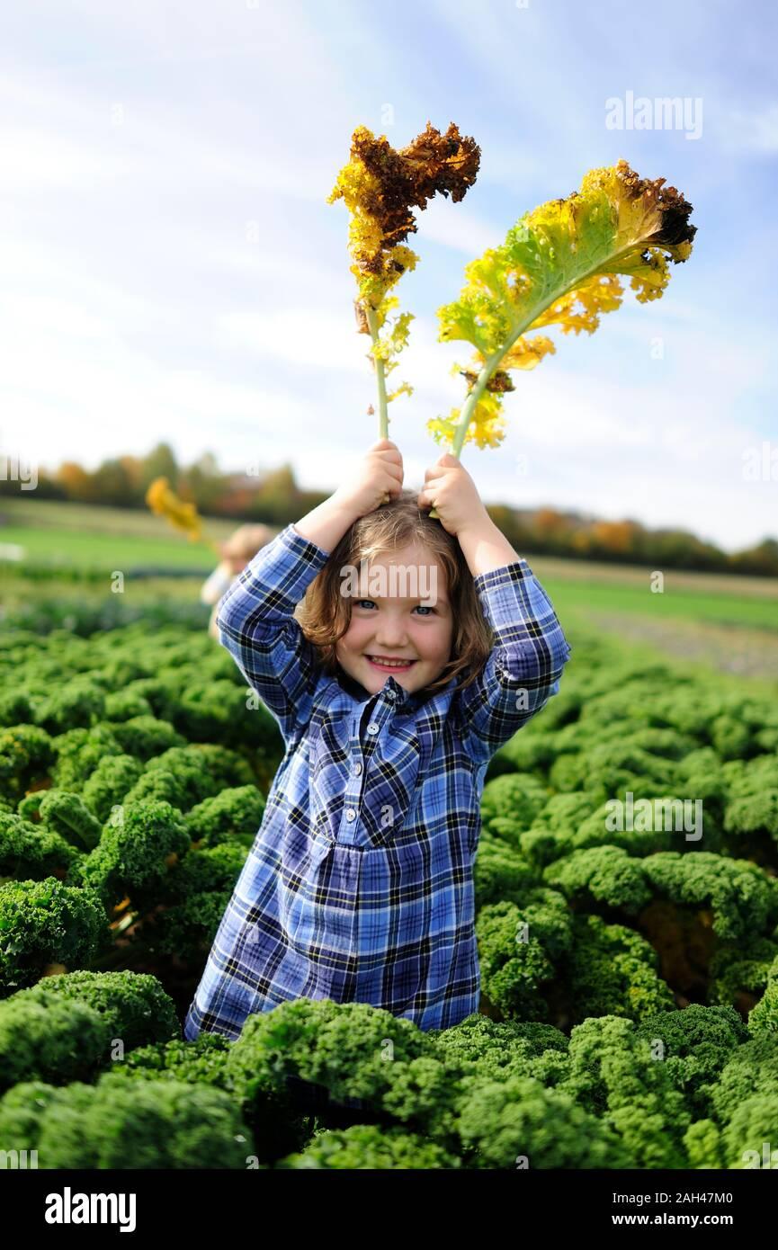 Girl in a kali field, leaves as rabbit ears Stock Photo