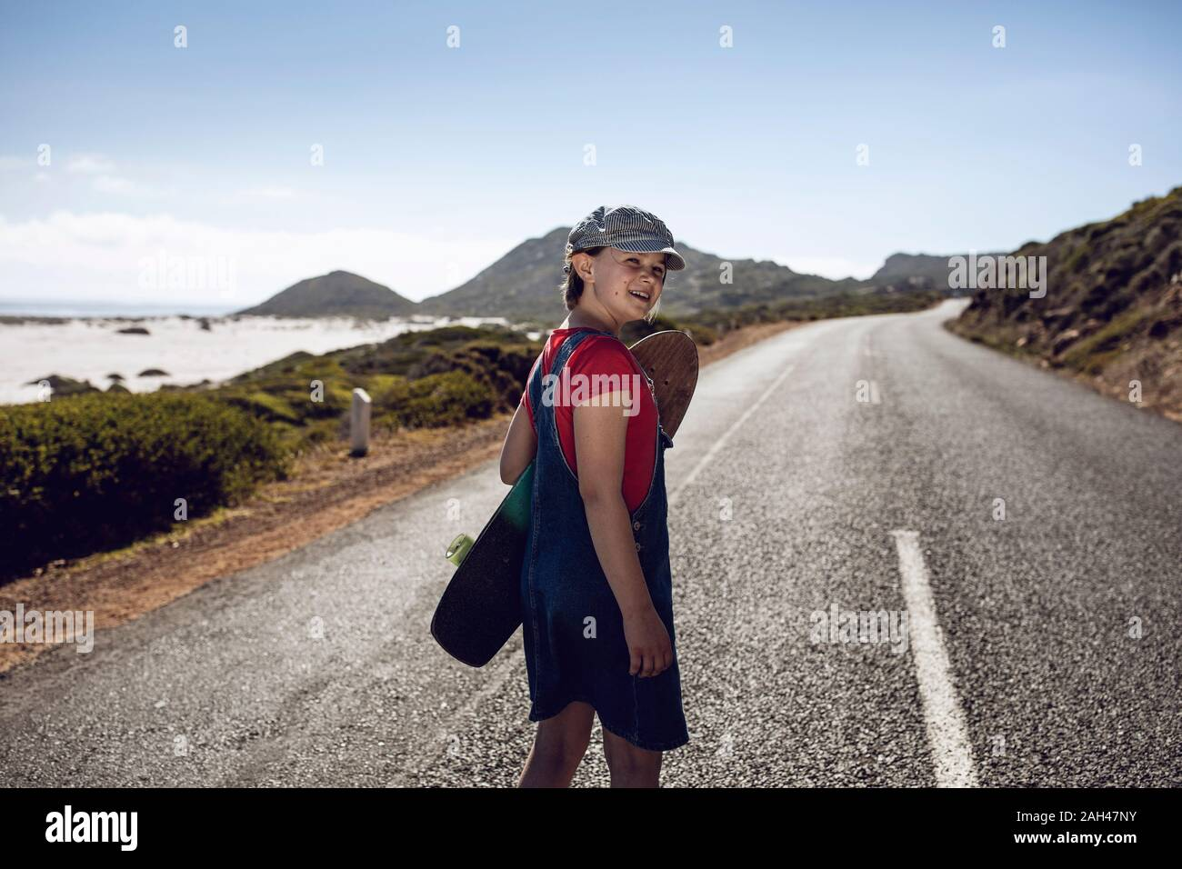 Portrait of smiling girl with skateboard standing on country road, Cape Town, Western Cape, South Africa Stock Photo