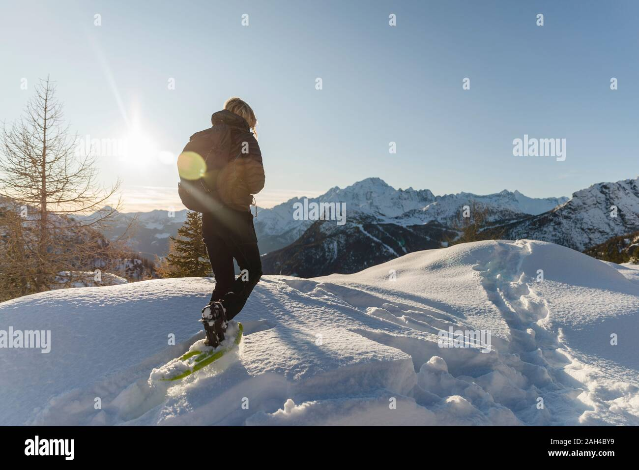 Woman walking with snowshoes in fresh snow in the mountains at sunset, Valmalenco, Italy Stock Photo