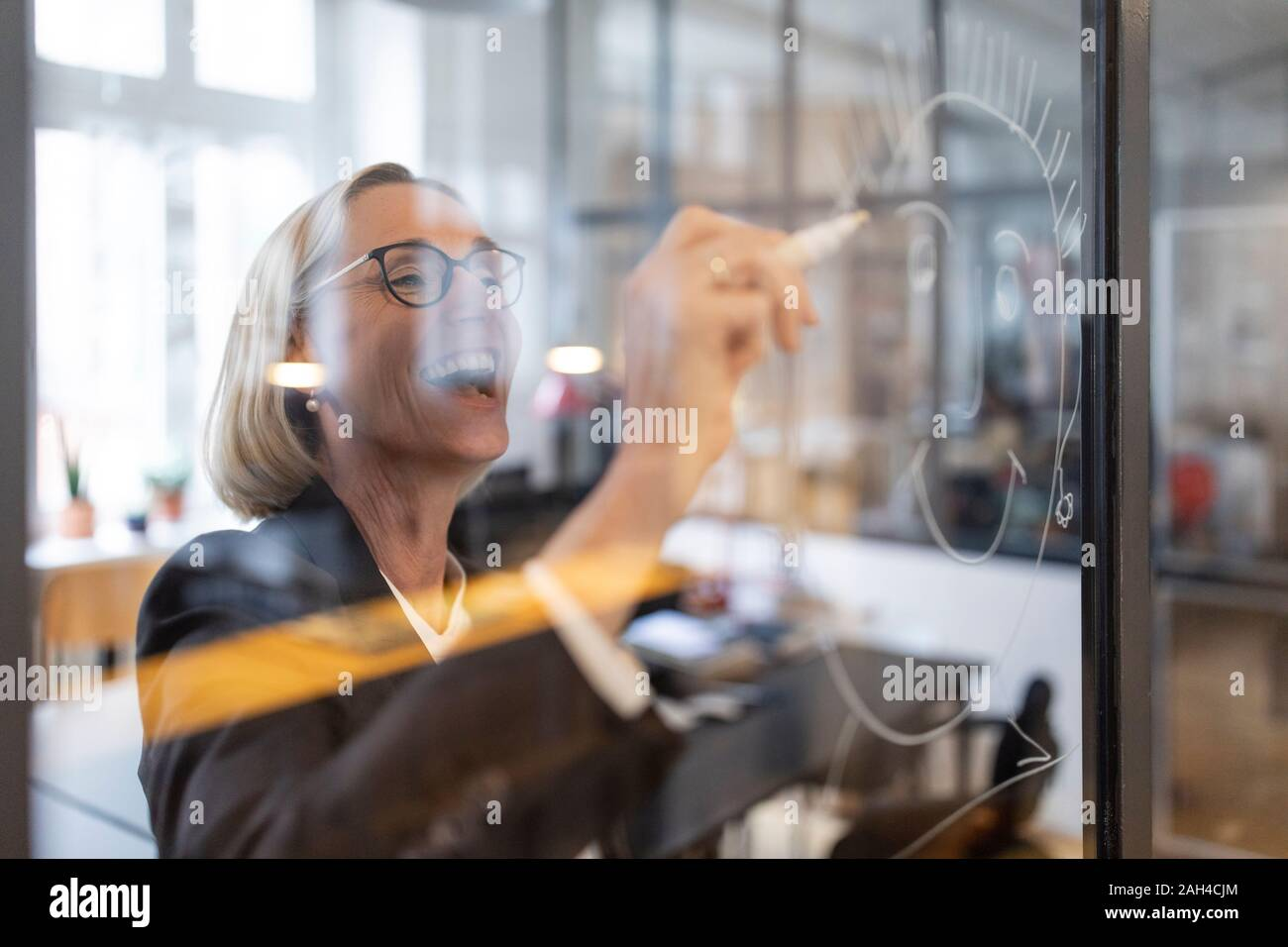 Happy mature businesswoman drawing face on glass pane in office Stock Photo