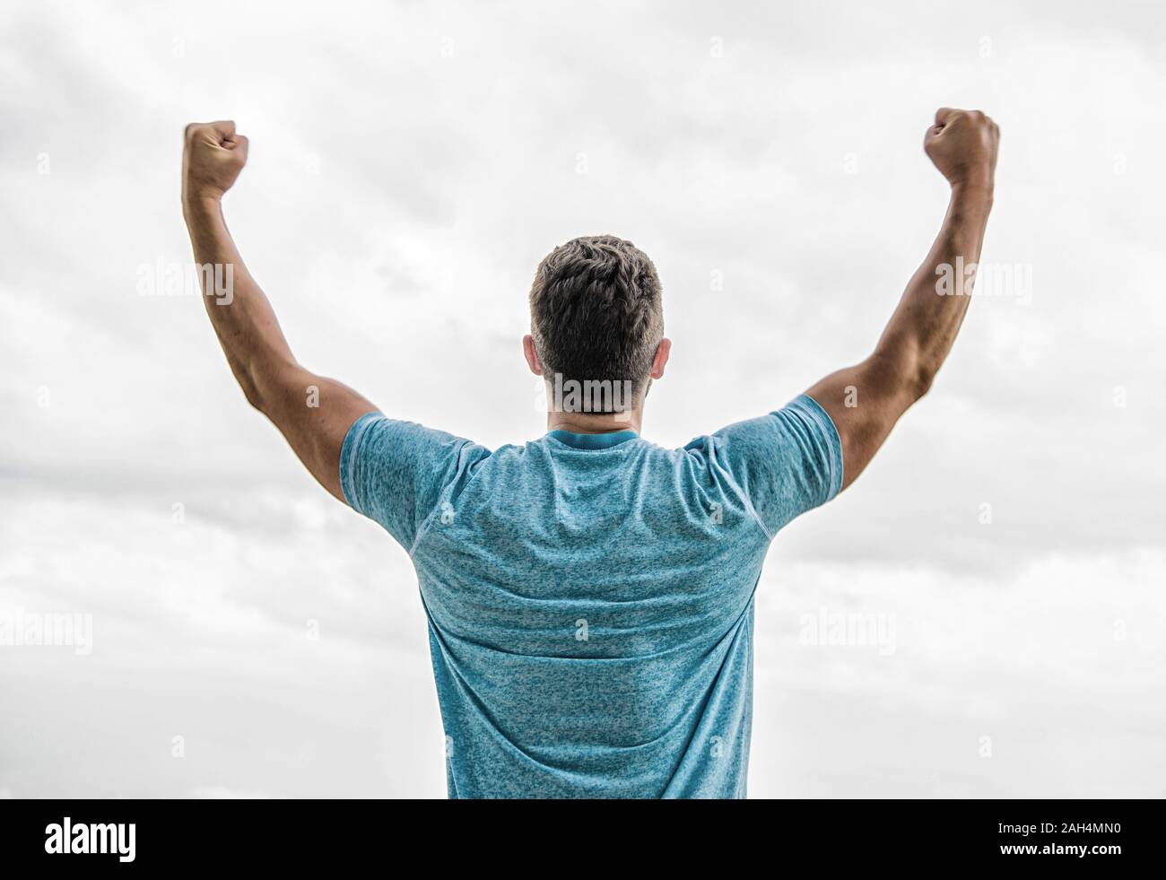 Victory and success. Champion winner. Future opportunity. Leadership and competition. Future concept. Looking forward in future. Strong muscular body feeling powerful rear view. Successful athlete. Stock Photo