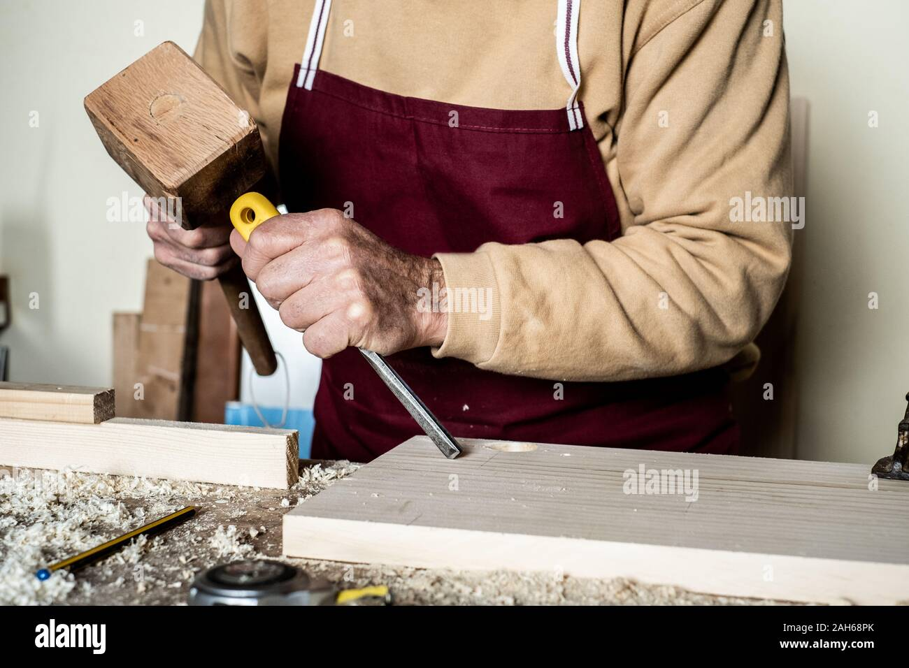 Carpenter's hands with chisel on the woodworking bench Stock Photo