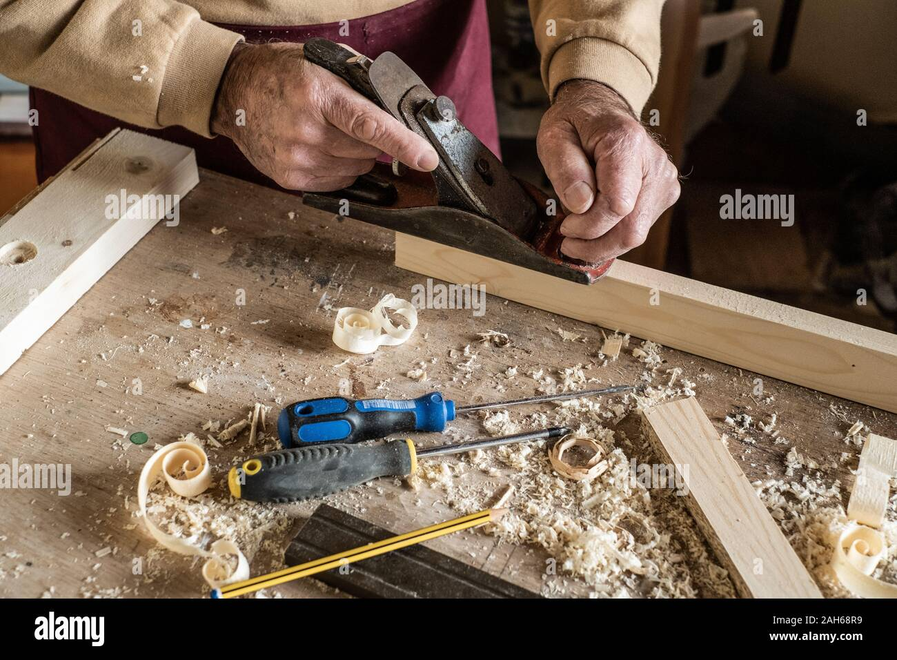 Carpenter man scraping curled wood scraps with hand plane tool and wooden plank. Stock Photo