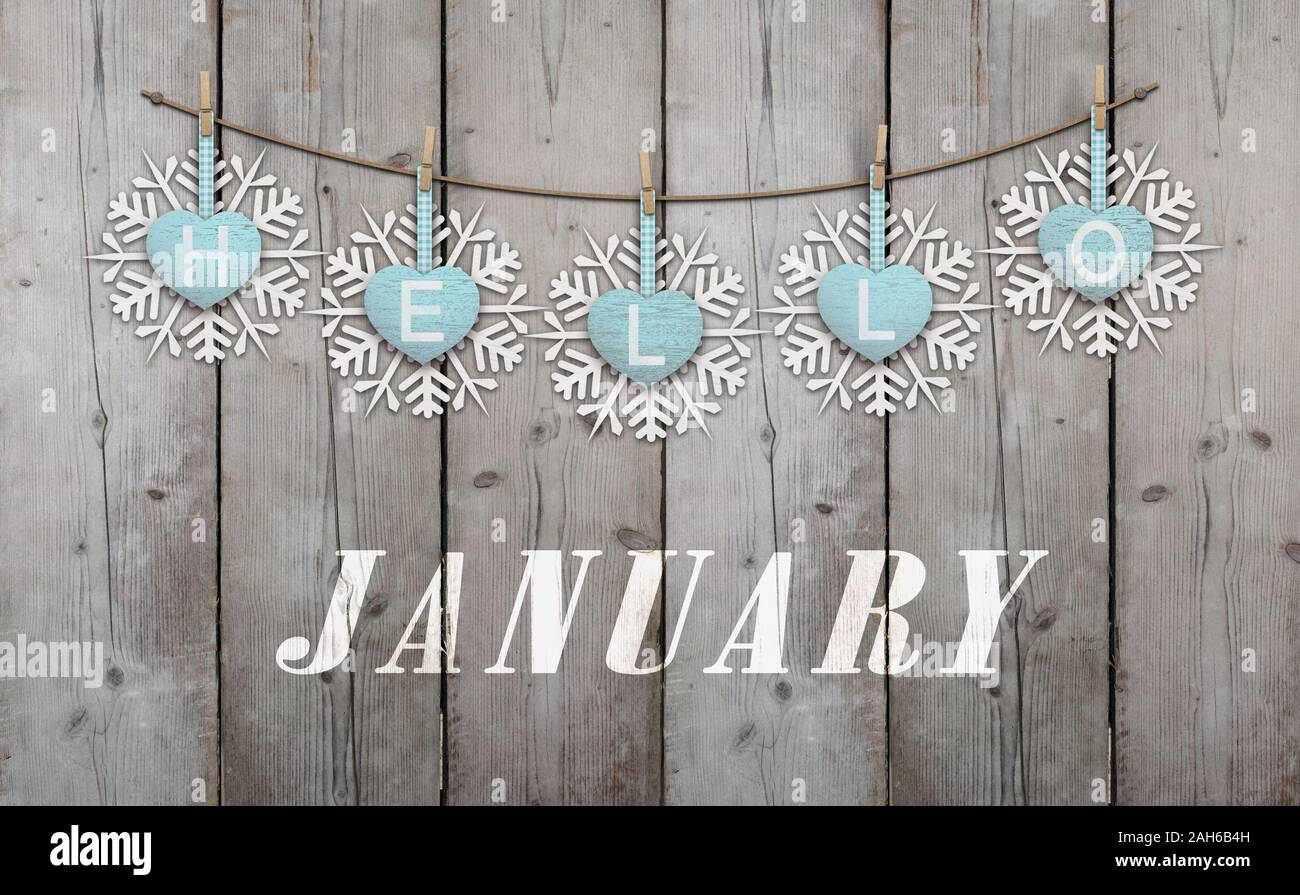 Hello january written on hanging ice blue hearts and white wooden snowflakes on weathered planks background Stock Photo