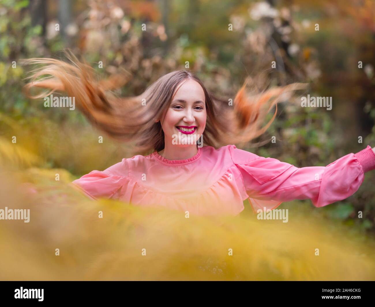 Country-girl countrygirl in countryside flying her hair wide apart portrait isolated partially blurry for happiness Stock Photo