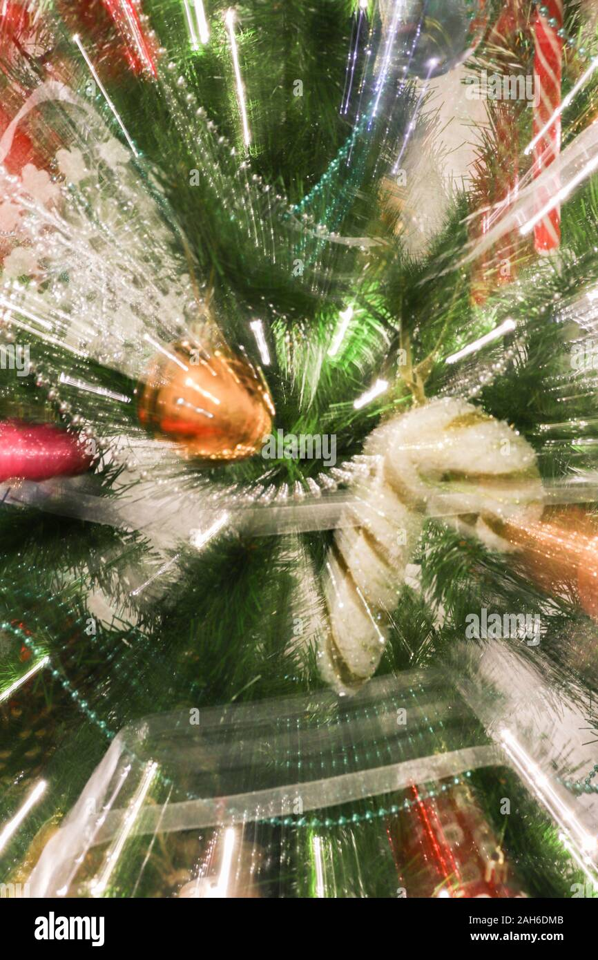 Abstract blurry photo of christmas tree with motion zoom effect, defocused colorful xmas ornaments. Stock Photo