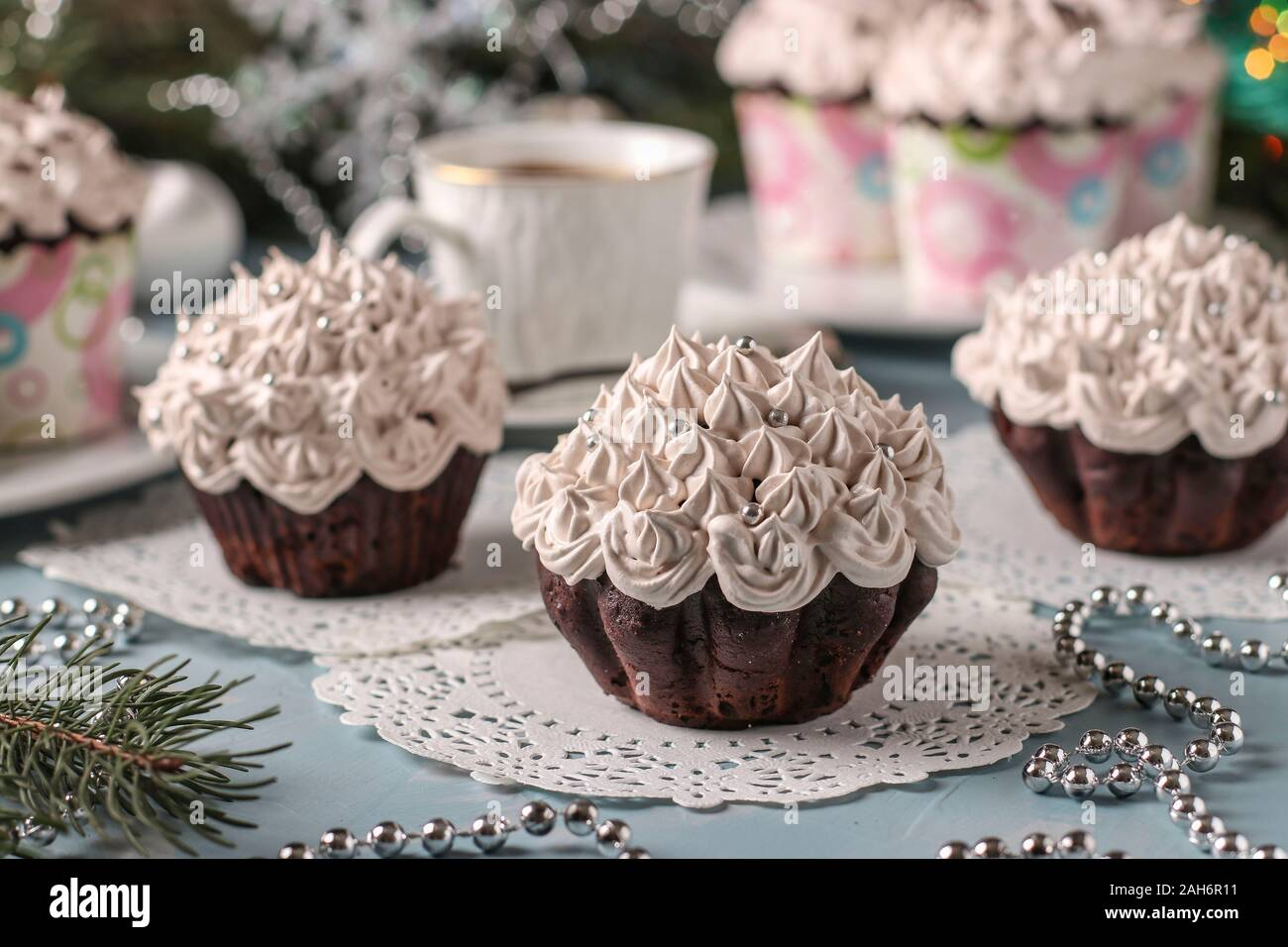 Homemade chocolate cupcakes with cream and a cup of coffee arranged on a light blue background, horizontal orientation Stock Photo