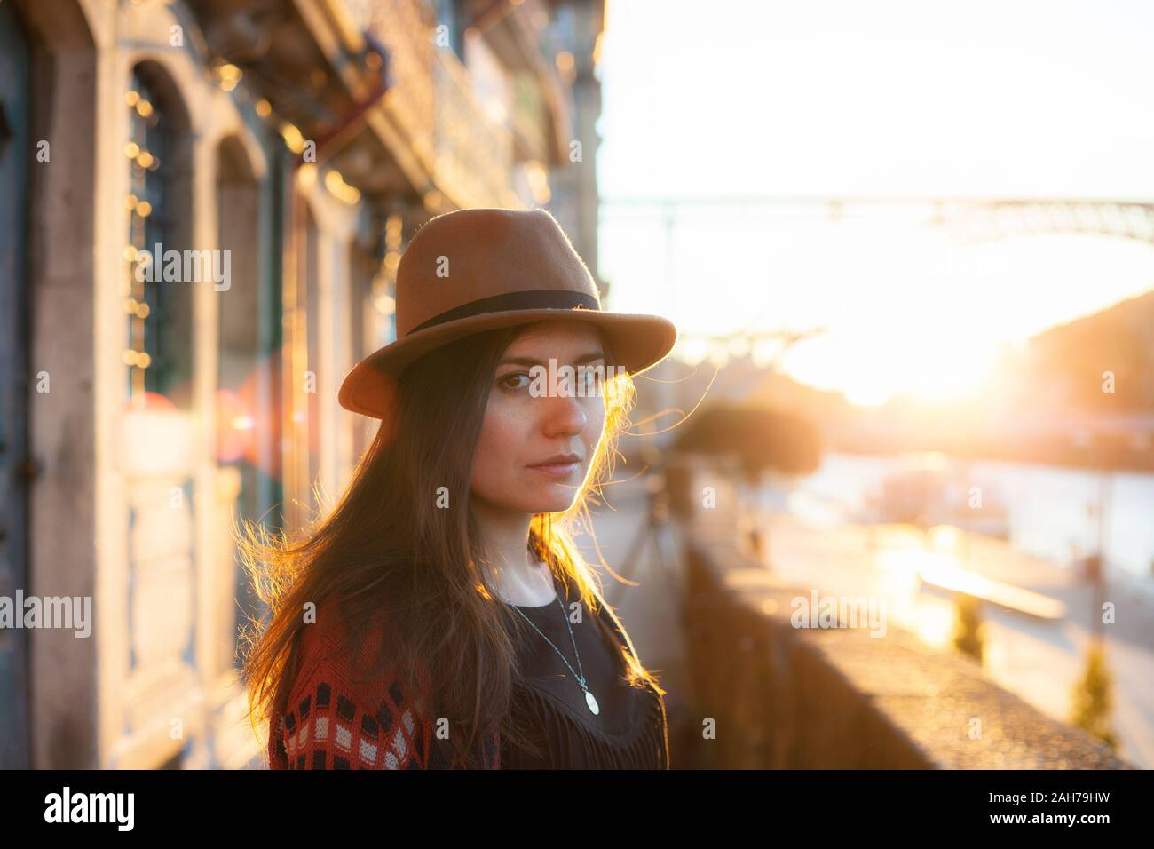 People, travel, holidays and adventure concept. Young woman with long hair walking on city street at sunrise, wearing hat and coat, enjoying happy ple Stock Photo