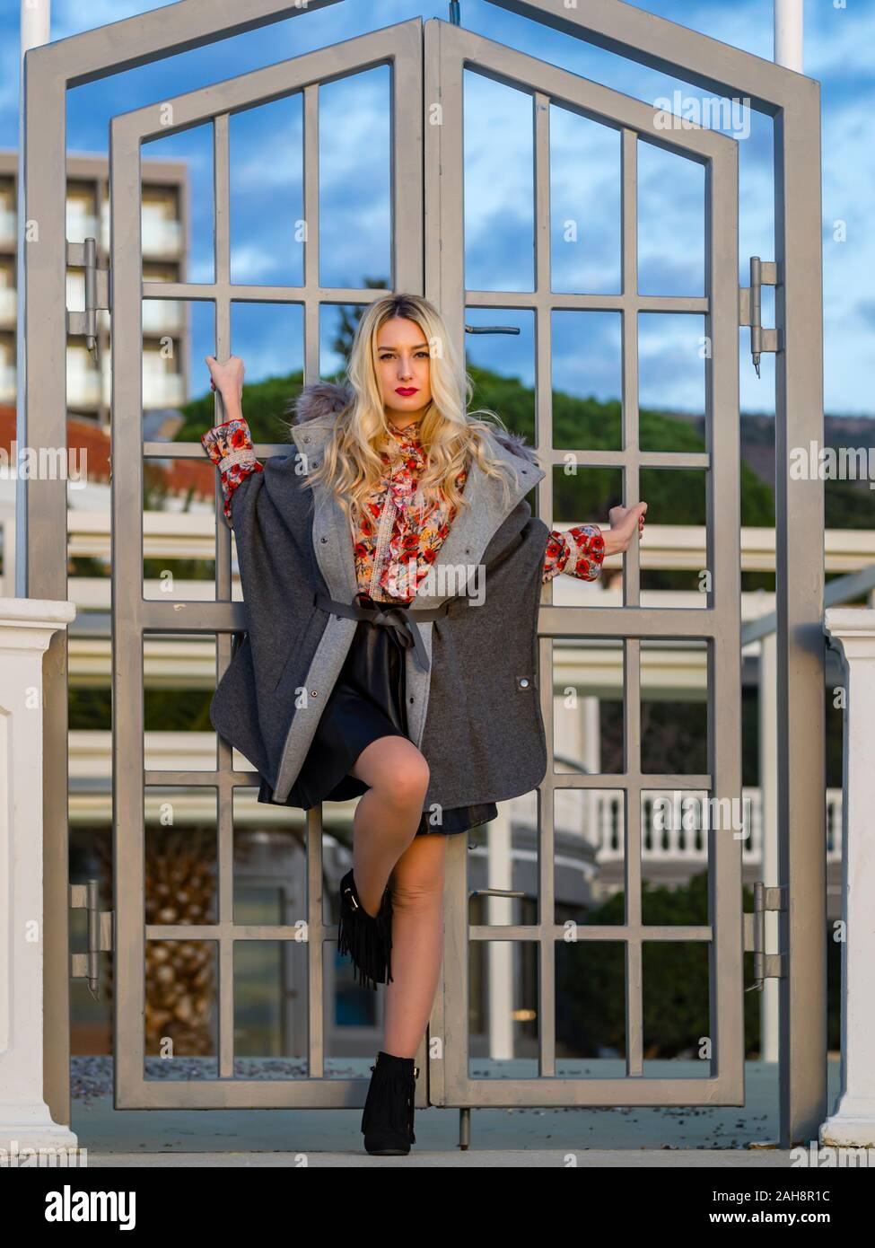 Fanciful blonde young lady spreading on metal fence door entrance looking at camera eyeshot eyes eye-contact serious facing frontal front view Stock Photo