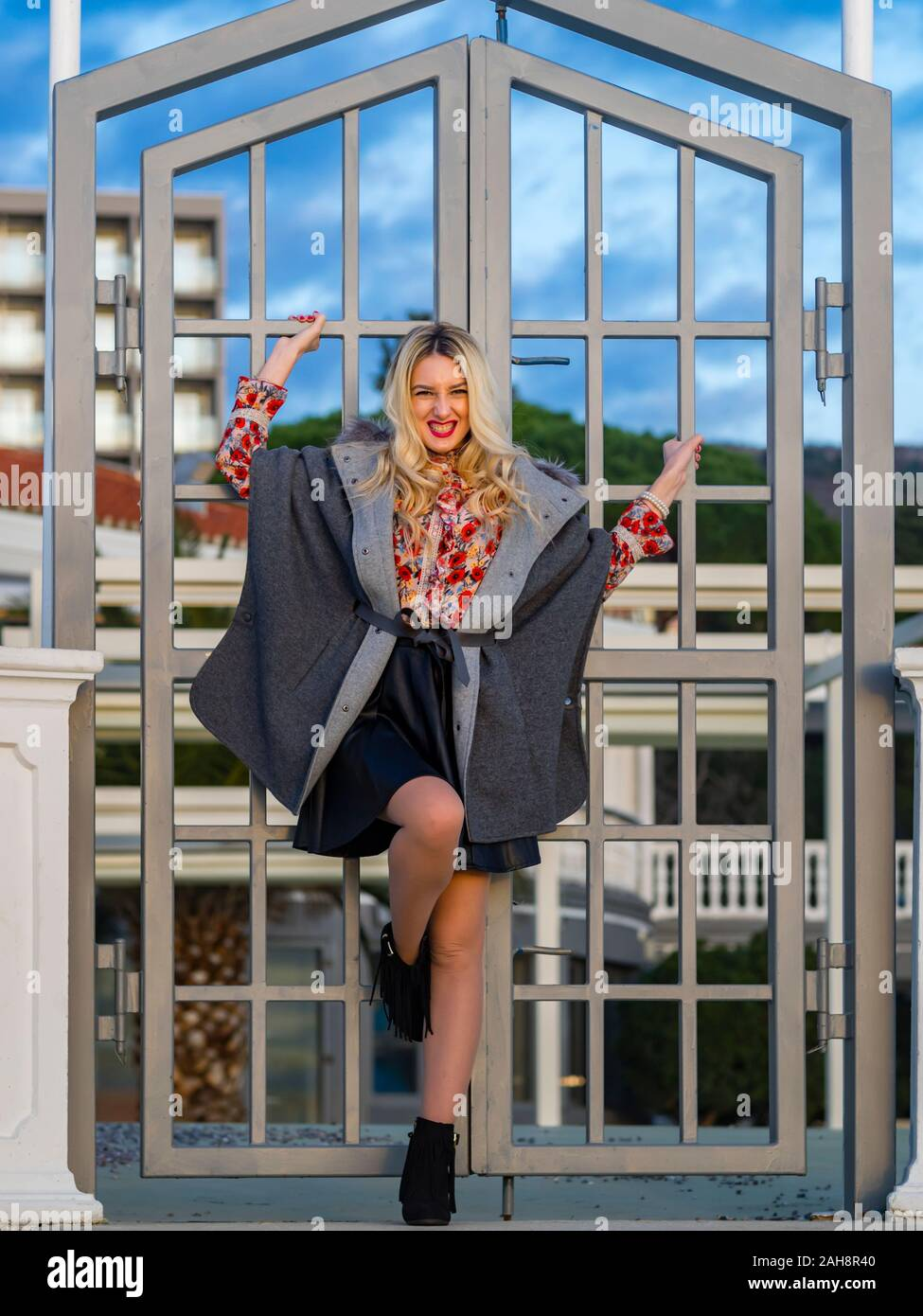Fanciful blonde young lady spreading on metal fence door entrance looking at camera eyeshot eyes eye-contact forsed chuckle smile Stock Photo