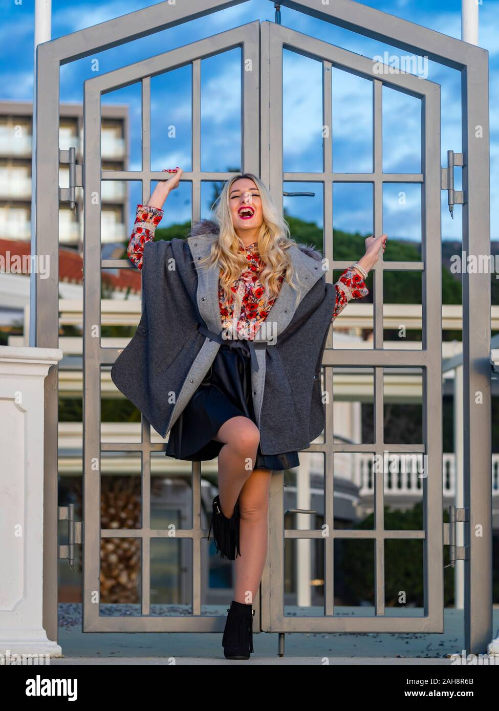 Fanciful blonde young lady spreading on metal fence door entrance looking at camera eyeshot eyes eye-contact hilarious laughing Stock Photo
