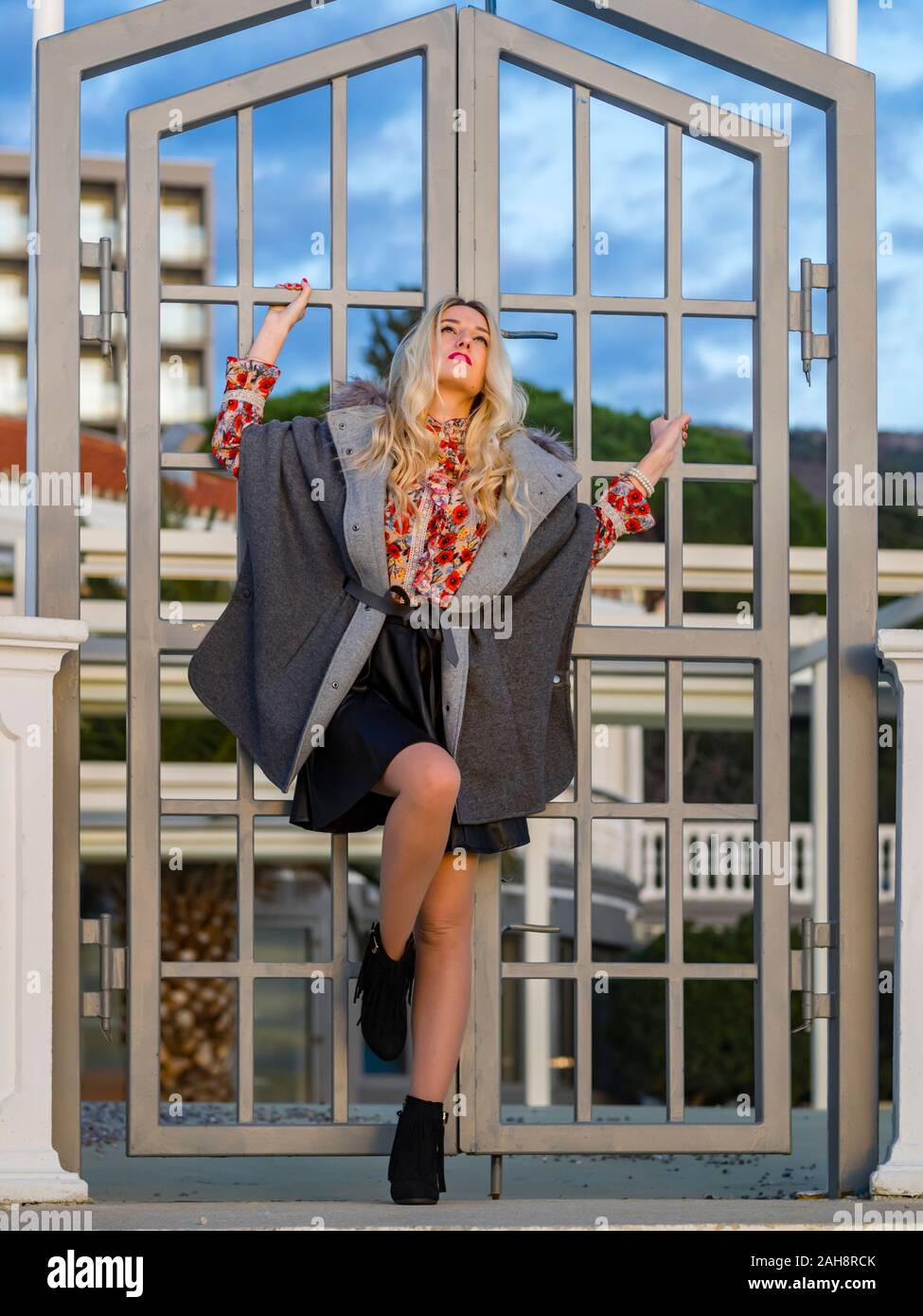 Fanciful blonde young lady spreading on metal fence door entrance to her back serious looking up upwards daydreaming day-dreaming daydreamer Stock Photo