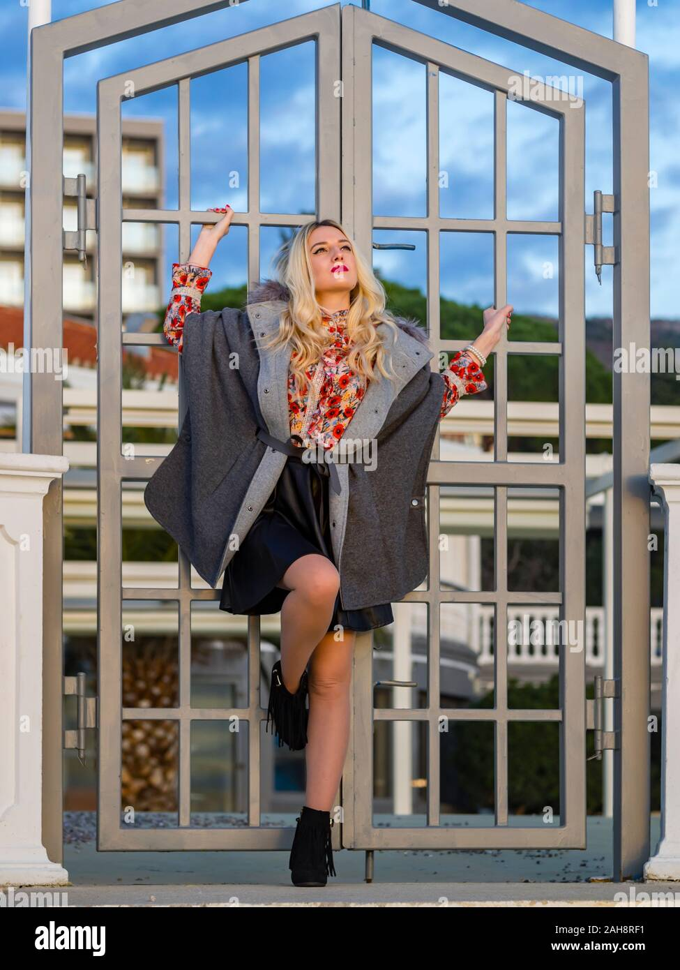 Fanciful blonde young lady spreading on metal fence door entrance serious looking up upwards daydreaming day-dreaming anticipating anticipate Stock Photo