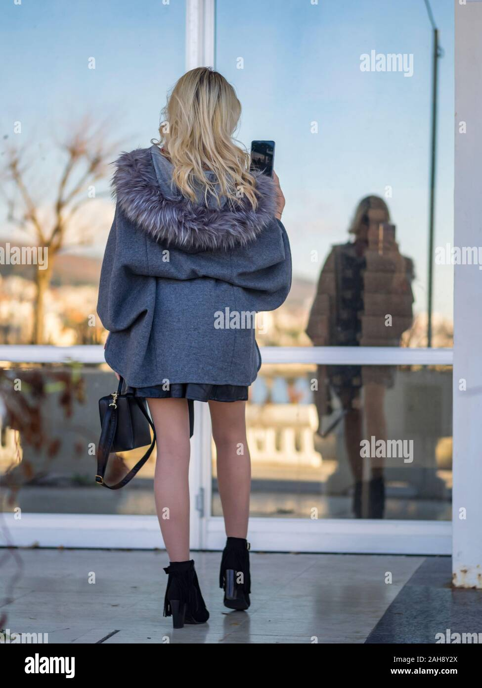 Fanciful blonde young lady is taking selfie in window glass reflection view from rear back behind Stock Photo