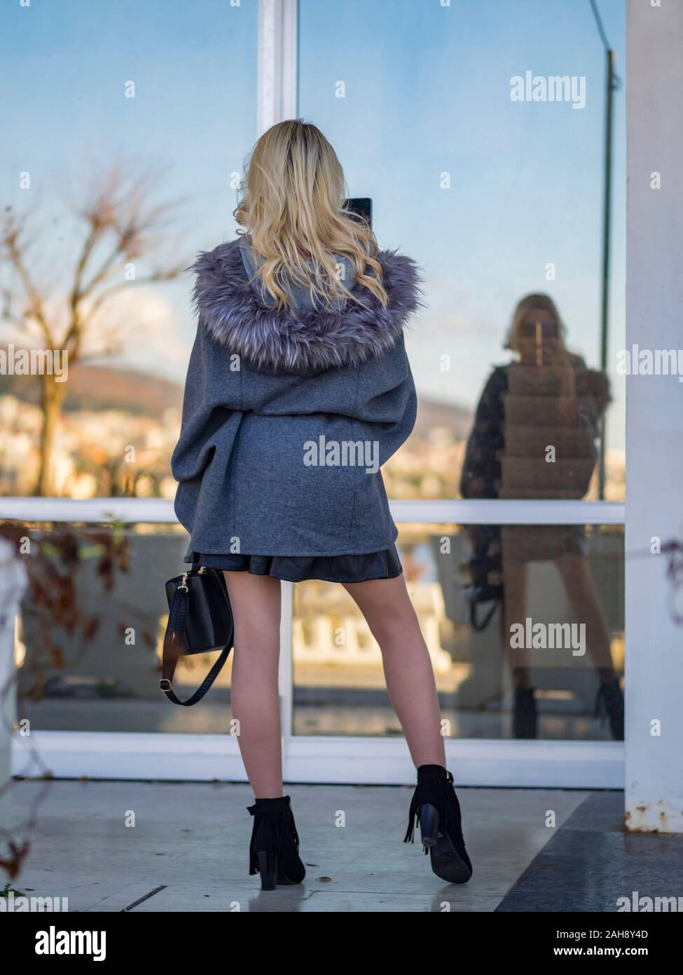 Fanciful blonde young lady is taking selfie in window glass reflection view from rear back behind model released release MR sleek Stock Photo