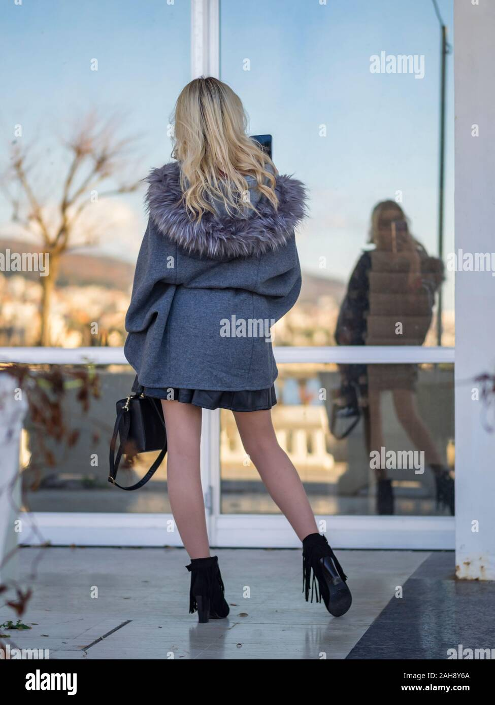 Fanciful blonde young lady is taking selfie for facebook in window glass reflection view from rear back behind with finesse Stock Photo