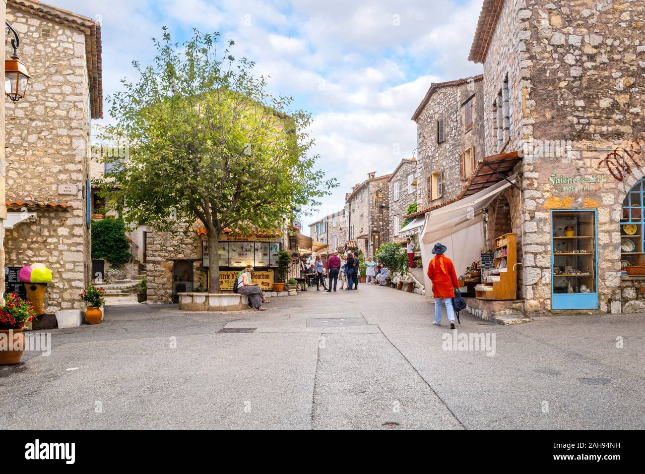 Tourists and locals fill the large square of shops and cafes inside the medieval hilltop village of Gourdon, France. Stock Photo