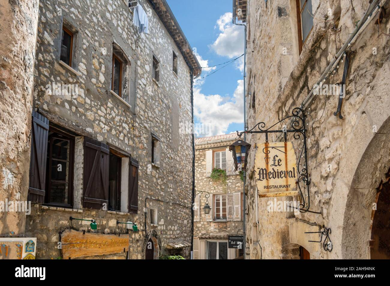 A quaint sign hangs on an ancient street inside the medieval walled stone village of Tourrettes Sur Loup in the Provence Alpes Maritimes area. Stock Photo
