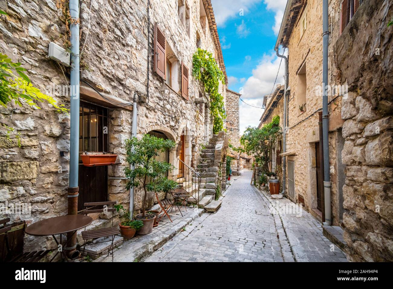 A picturesque back street of homes and apartments in the medieval village of Tourrettes Sur Loup in the Alpes Maritimes area of Southern France. Stock Photo