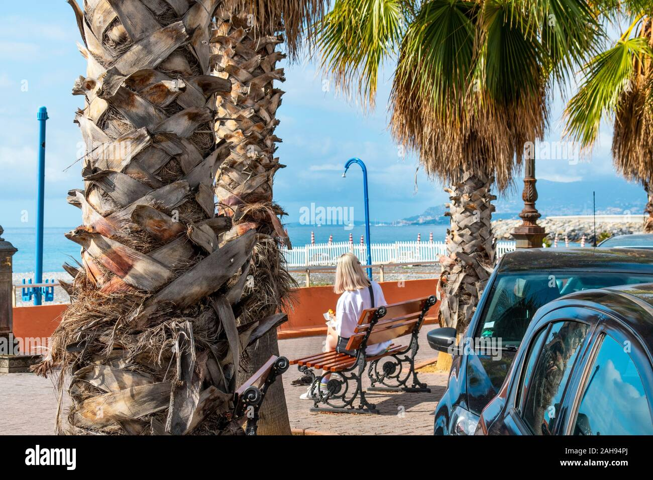An unidentifiable woman eats her lunch on a park bench in front of the Mediterranean Sea at the coastal town of Ventimiglia, Italy, on the Riviera. Stock Photo