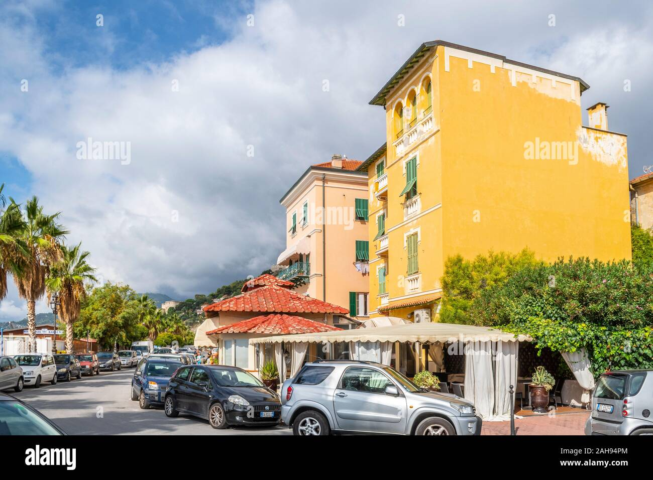 Parked cars line both sides of a narrow street at the Mediterranean coastal resort of Ventimiglia, Italy, on the Italian Riviera. Stock Photo