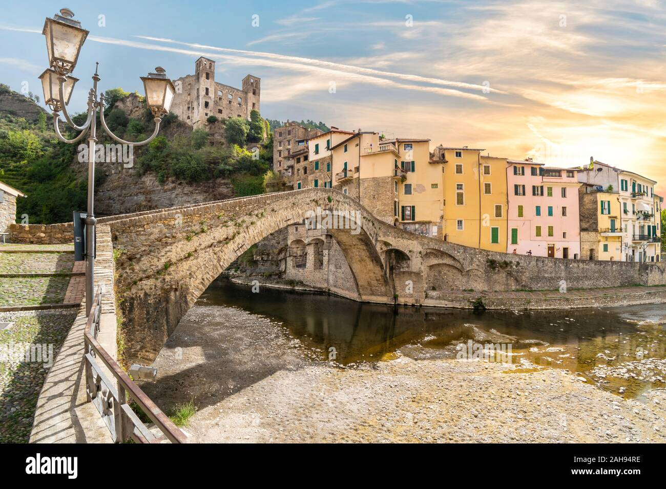 The colorful hilltop, medieval village of Dolceacqua, Italy, with it's famous castle and stone Monet bridge as the sun sets. Stock Photo