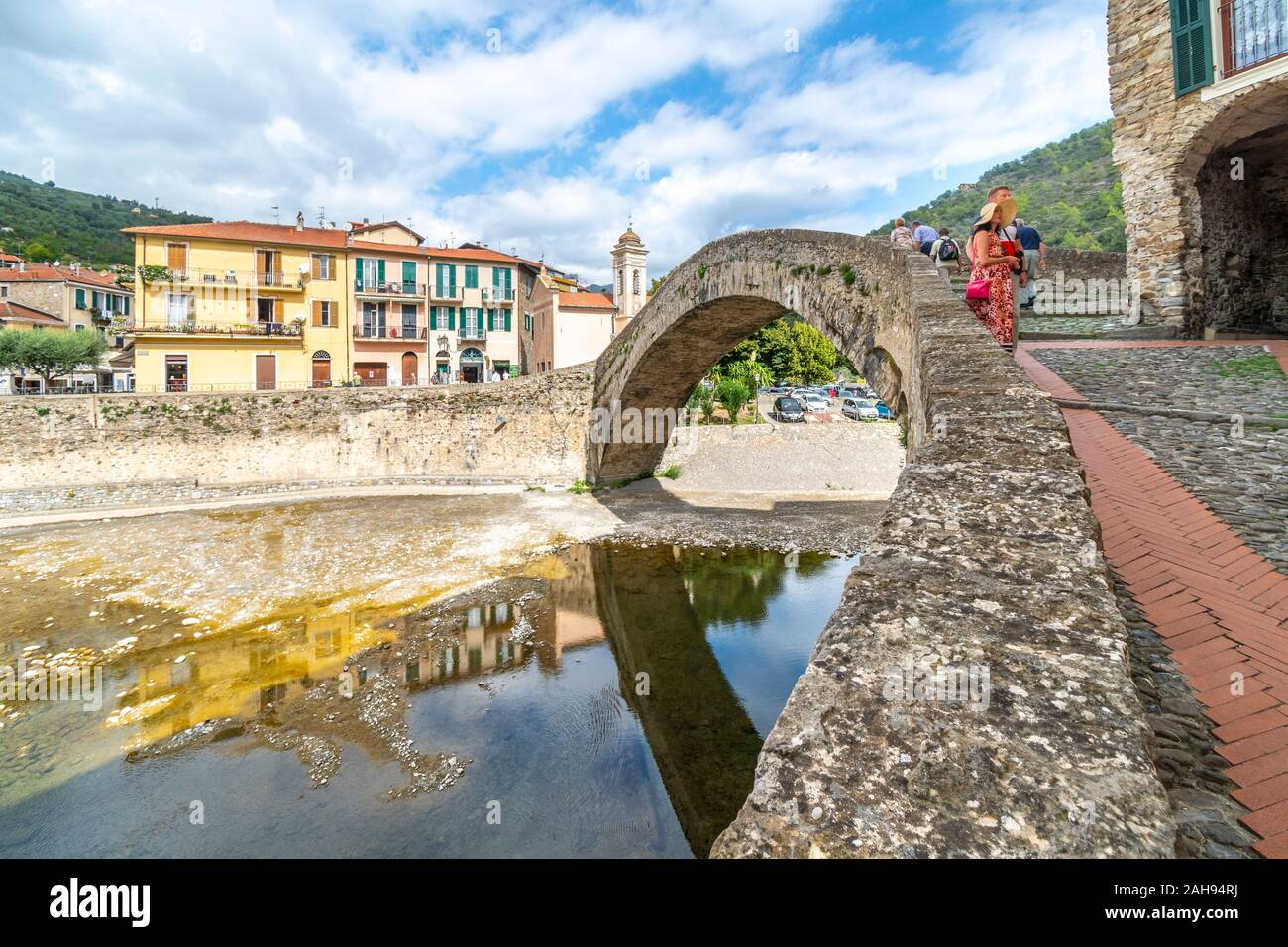 Tourists, including an attractive younger couple, sightsee near the Monet arched bridge in the medieval village of Dolceacqua, Italy. Stock Photo