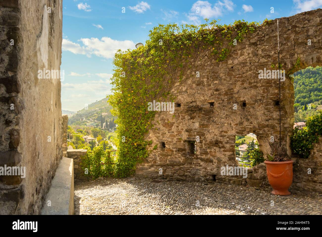 A courtyard with views of the Ligurian mountains and ancient wall covered with ivy at the top of the Dolceacqua Castle in Italy Stock Photo