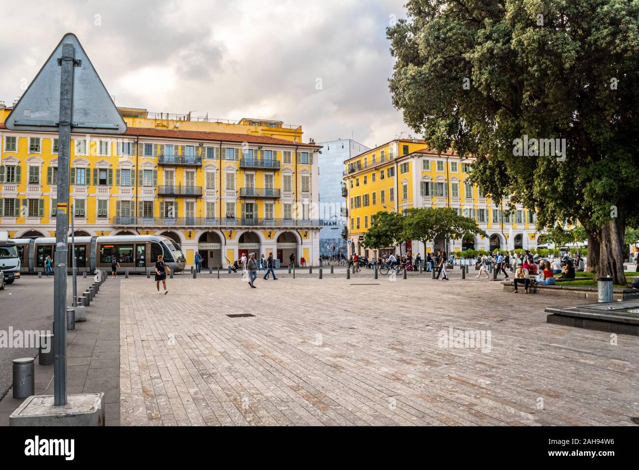 Local French men and women relax near the water fountain and statue in Place Garibaldi as a tram goes by in central Nice, France. Stock Photo