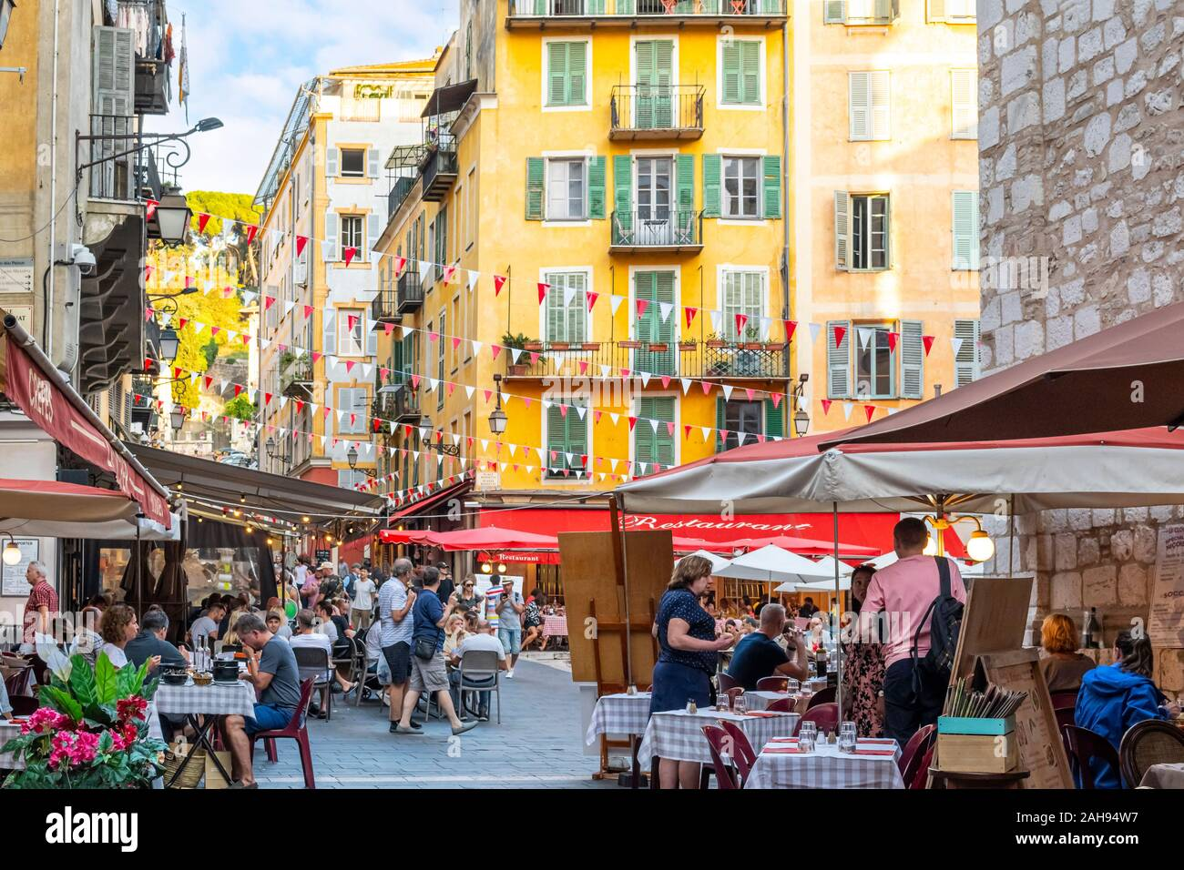 A busy later afternoon at the colorfully decorated Place Rossetti as tourists crowd the shops and cafes in the Old Town area. Stock Photo