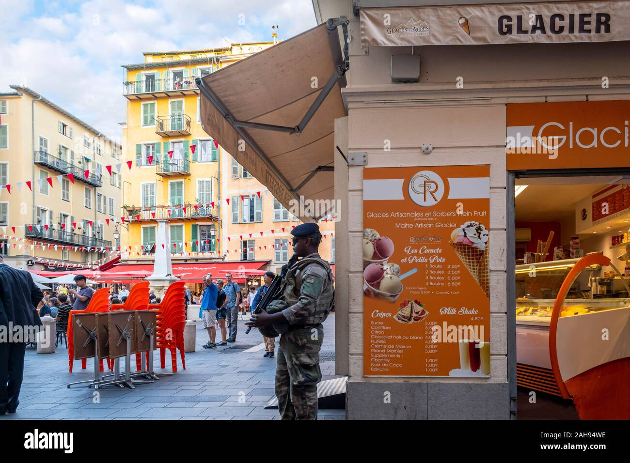 A young black male French army security officer with a beret and automatic rifle stands guard inside city center in Nice, France. Stock Photo