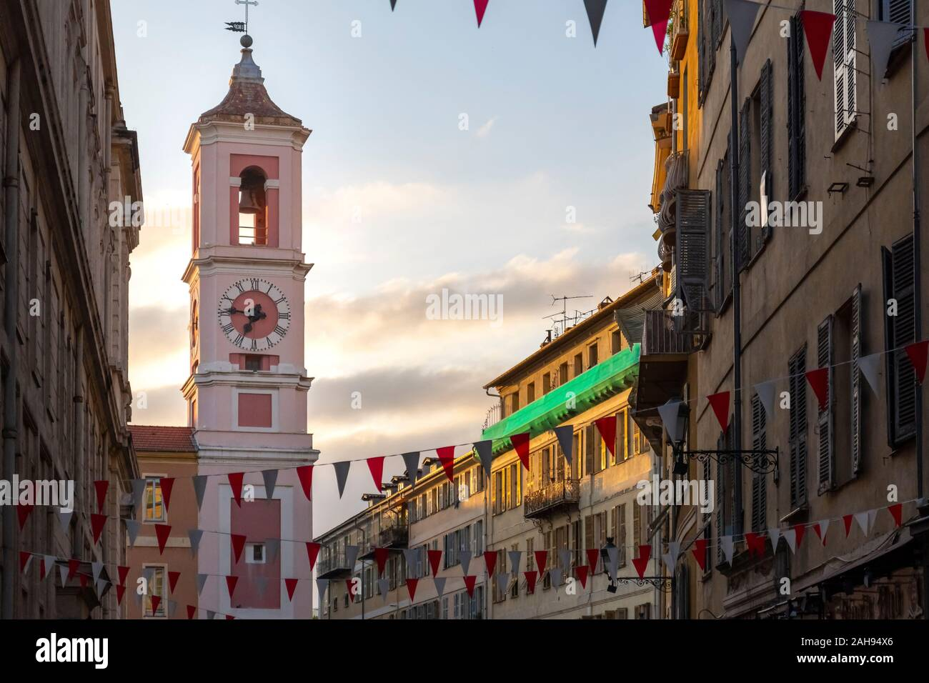 Evening view of the Rusca Palace Clock Tower at the Place du Palais du Justice with red and white flags draped over the street in Nice, France Stock Photo