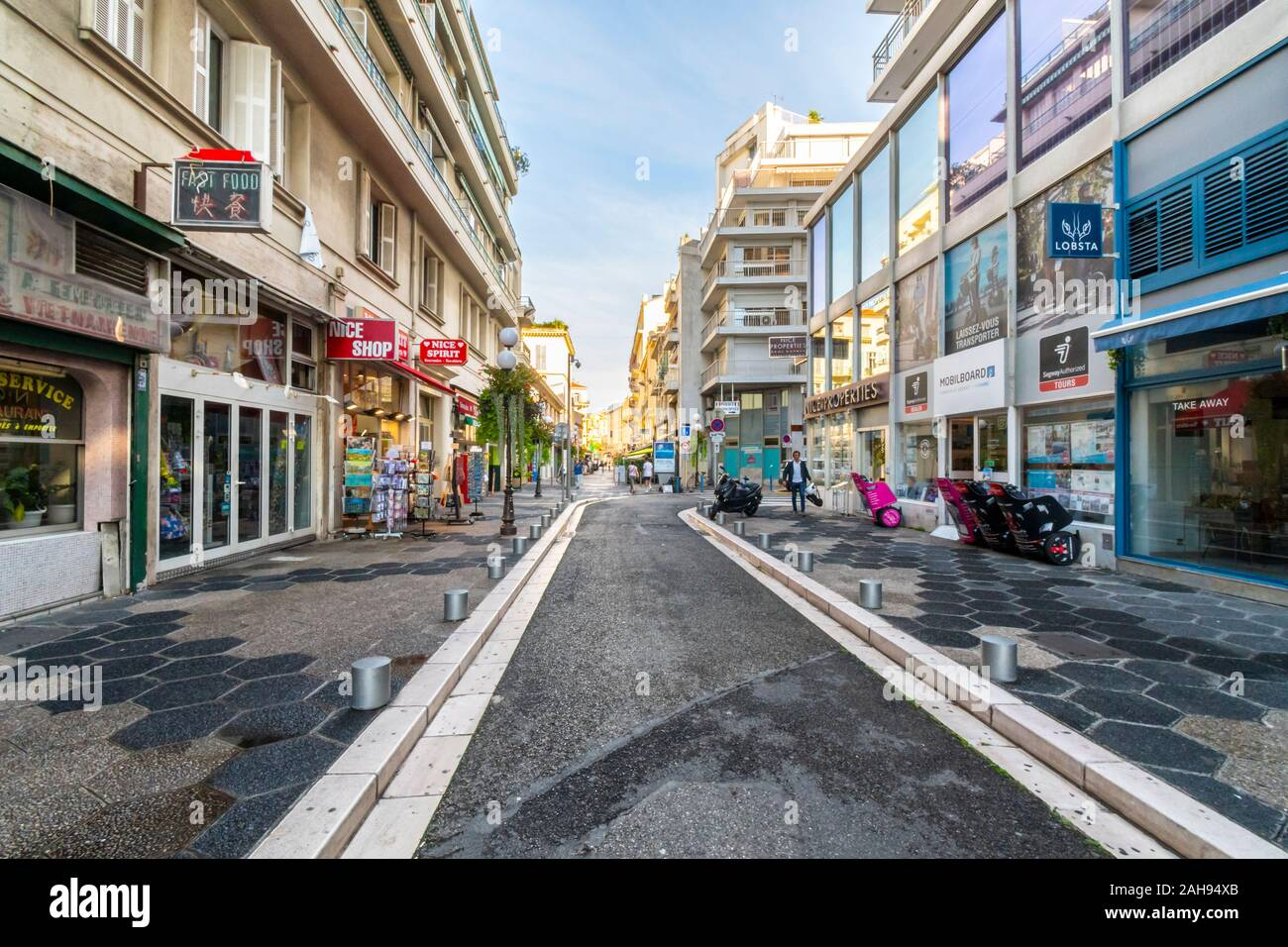 A lone pedestrian walks down side street early on a weekday morning in the city of Nice, France, on the French Riviera. Stock Photo