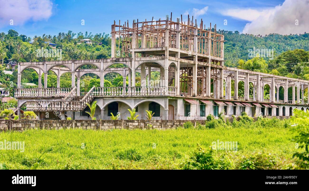 A failed tourism project in the Philippines, resulting in an abandoned hotel construction site in a former rice paddy, after the owner ran out of cash Stock Photo