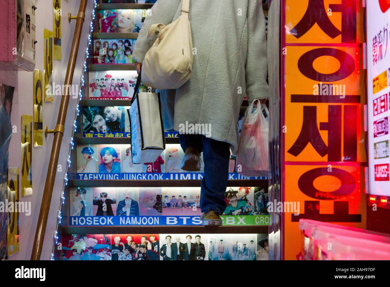 A woman carrying shopping bags climbs stairs with pictures of Korean idols and celebrities on them in a shop in Shin-Okubo, Shinjuku, Tokyo, Japan. Stock Photo