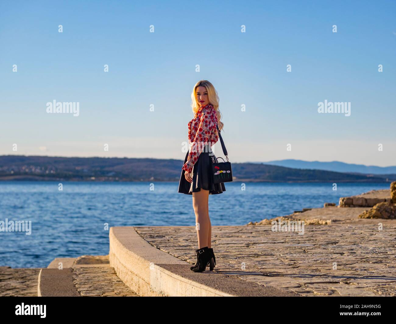 Fanciful blonde young lady standing seaside woman serious looking at camera eyeshot eyes eye-contact MR model-released release figure profile sleek Stock Photo