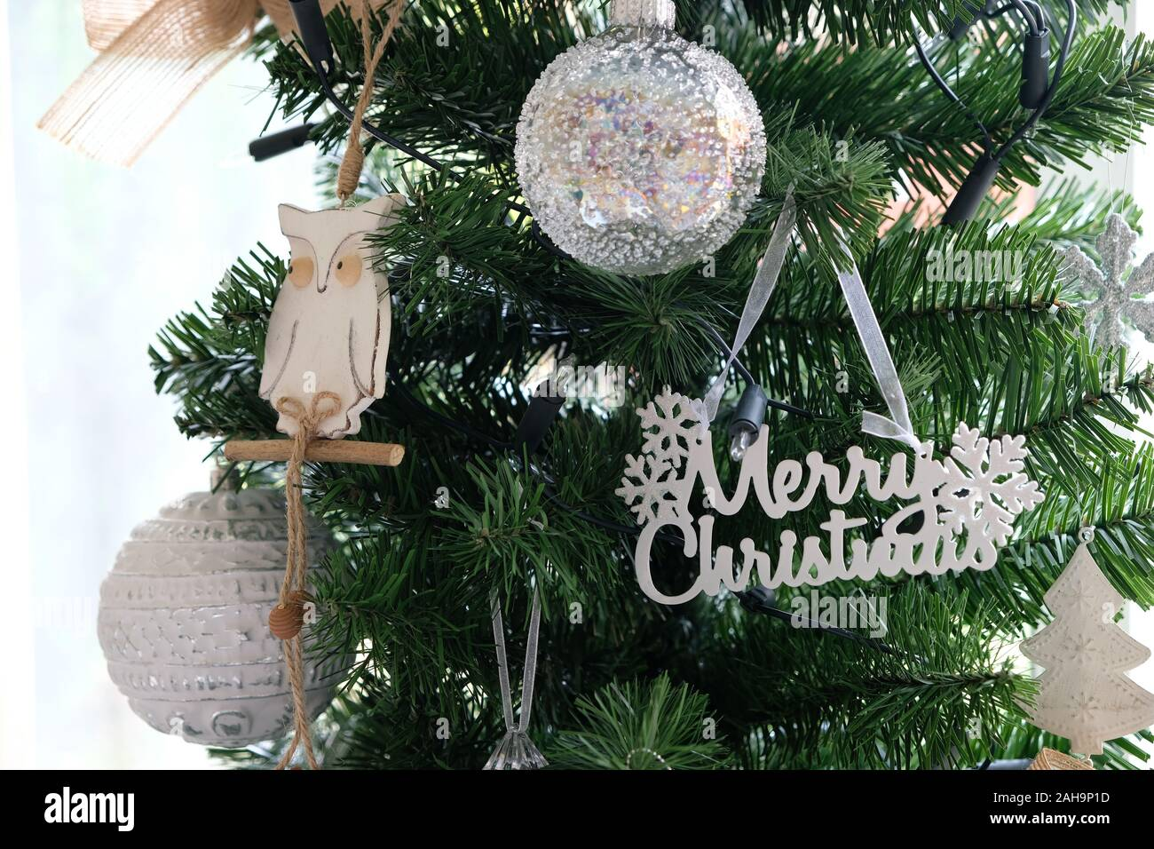 December 2019 White And Silver Christmas Decorations Hang On A Traditional Artificial Green Christmas Tree Stock Photo Alamy