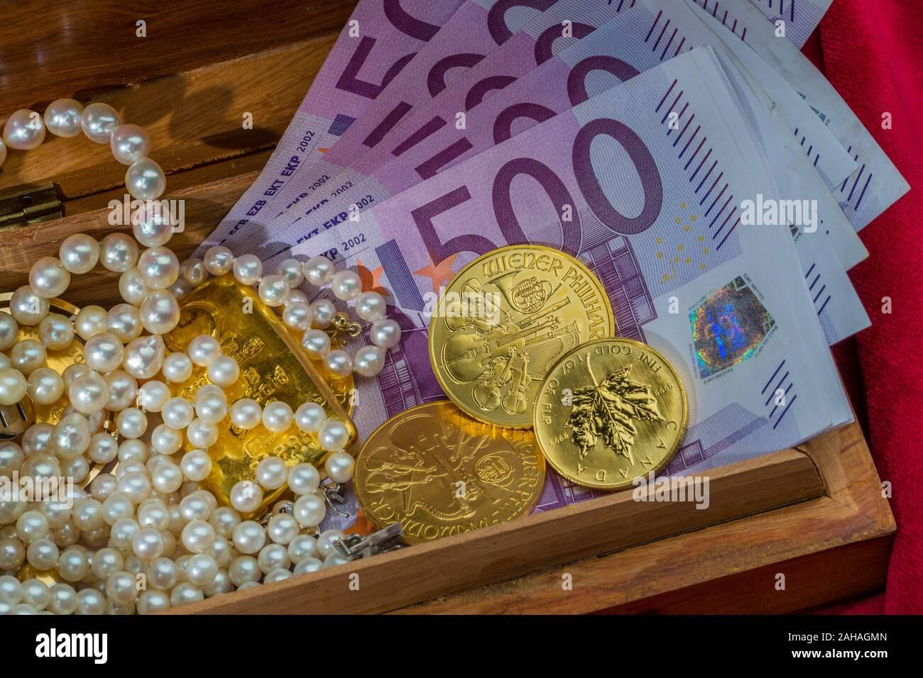 Gold in Münzen und Barren mit Schmuck auf rotem Samt. Symbolfoto für Reichtum, Luxus, Reichensteuer, 500 Euro Scheine, Stock Photo