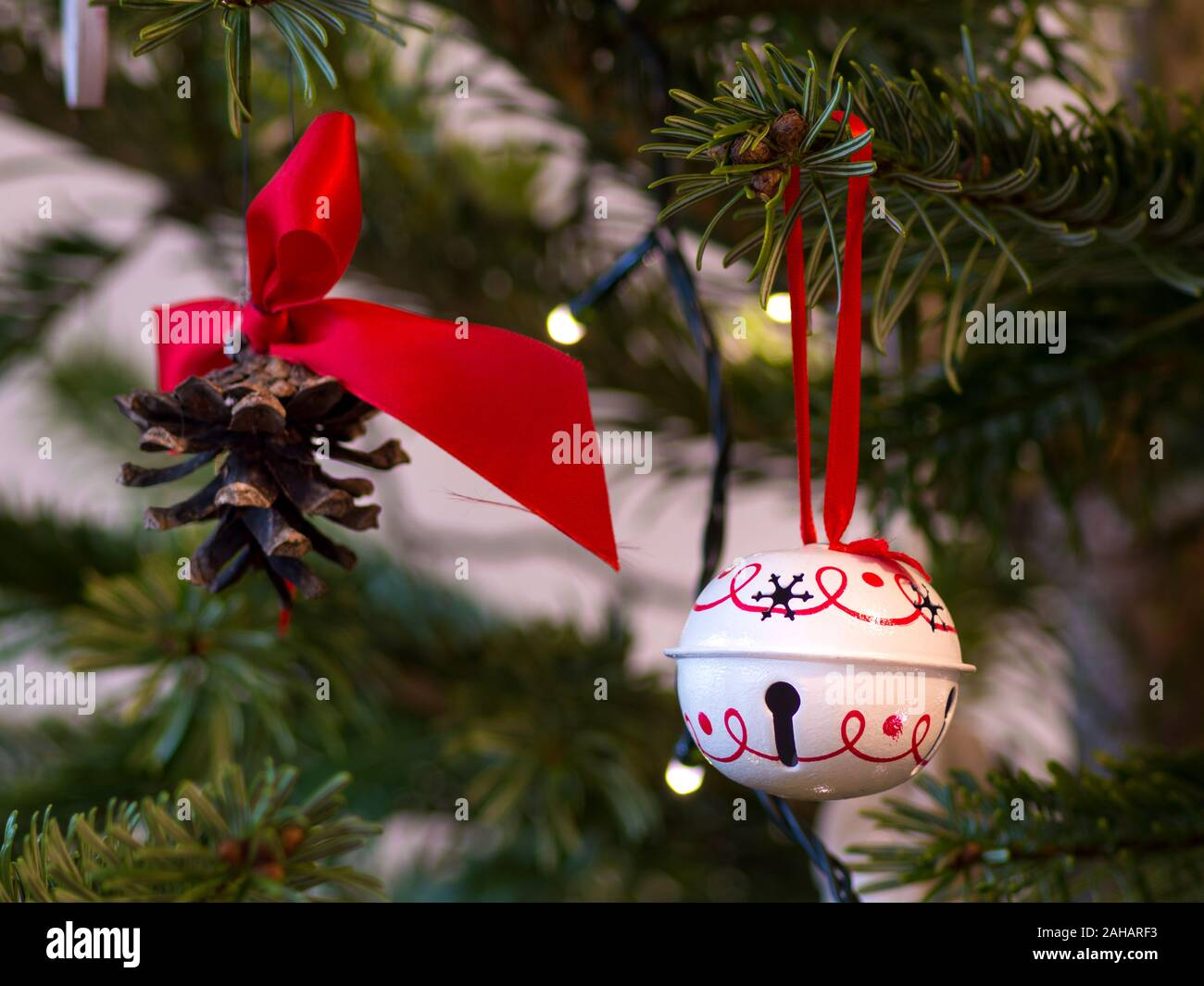 Pinecone with a red ribbon and a white round decoration on a green ...