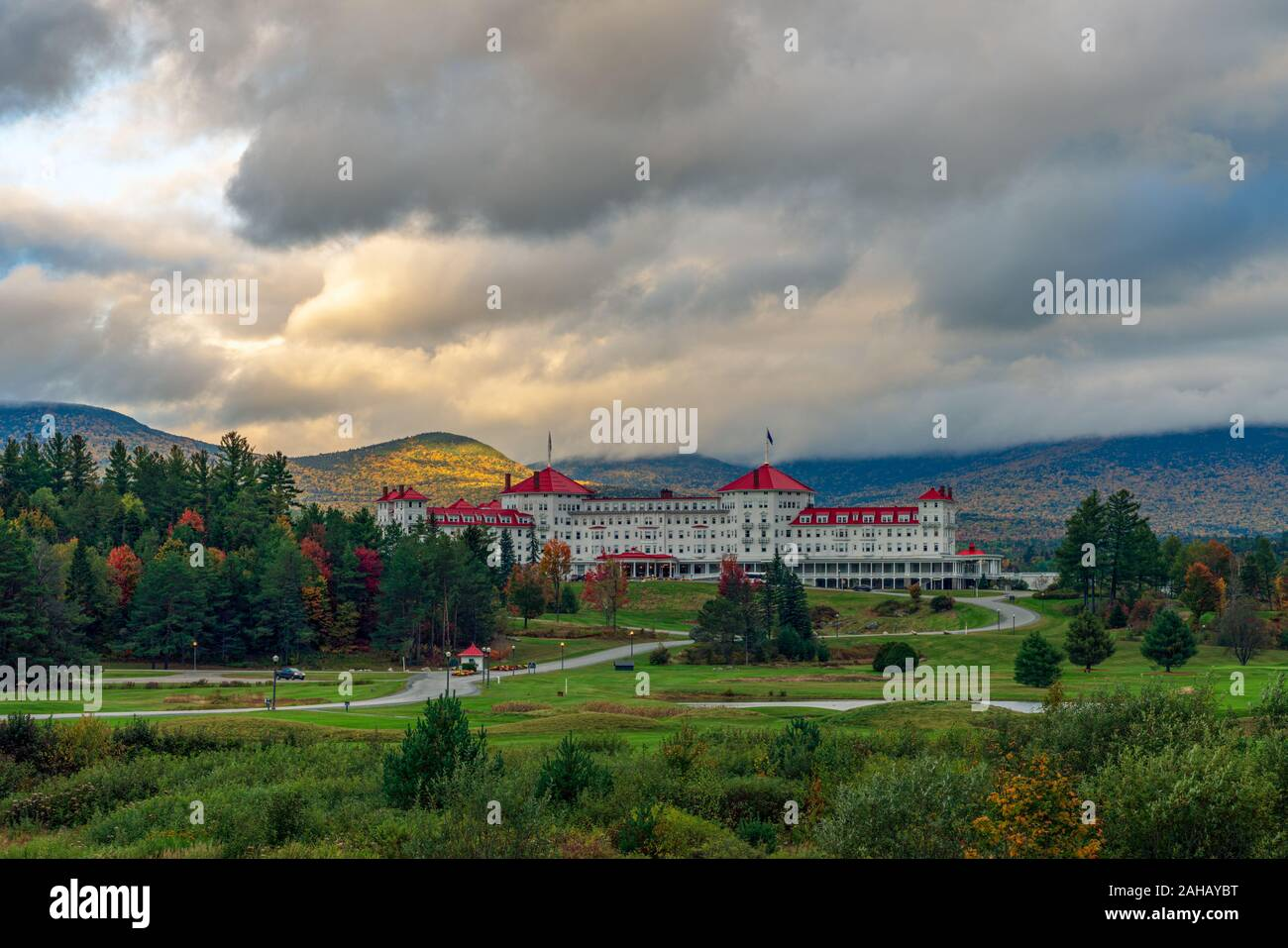 A break in the clouds allows golden sunlight to illuminate the mountside behind the iconic Mount Washington Hotel. Stock Photo