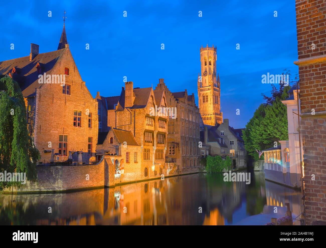 Famous view of Bruges tourist landmark attraction - Rozenhoedkaai canal with Belfry and old houses along canal with tree in the night. Belgium Stock Photo