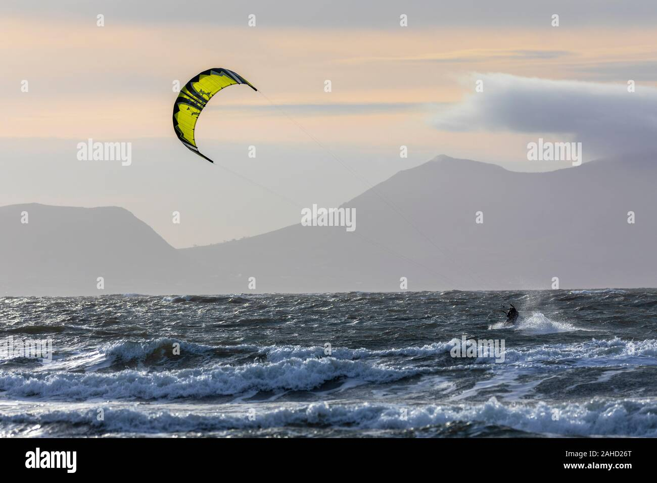 Anglesey, North Wales, 28tht December 2019. UK Weather:  Mild and windy weather at Newborough Beach on the west coast of Anglesey, with speed restrictions on bridges crossing to the island.  Flintshire, Wales. A kite boarder making use of the windy conditions at Newborough Beach with a backdrop of the coastal mountains on the mainland in the distance, Anglesey, Wales © DGDImages/AlamyLiveNews Stock Photo